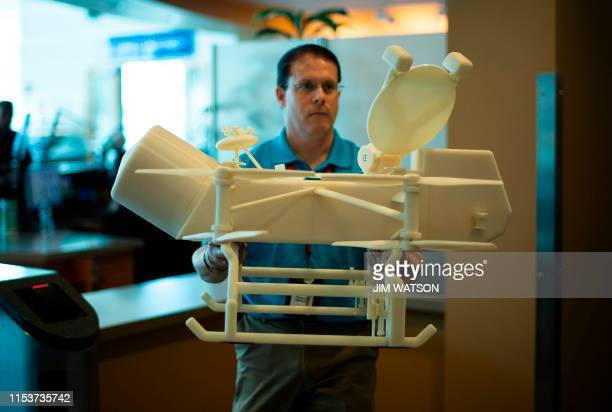 Ken Hibbard Mission Systems Engineer for the Dragonfly mission walks to his office carrying the one quarter scale 3Dprinted model of the quadcopter...