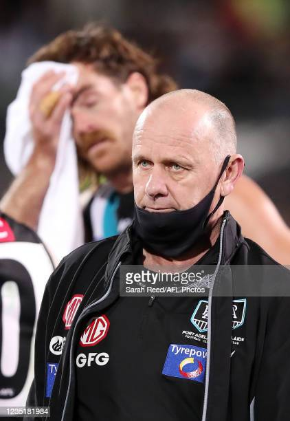 Ken Hinkley, Senior Coach of the Power at quarter time with Scott Lycett in the background during the 2021 AFL Second Preliminary Final match between...