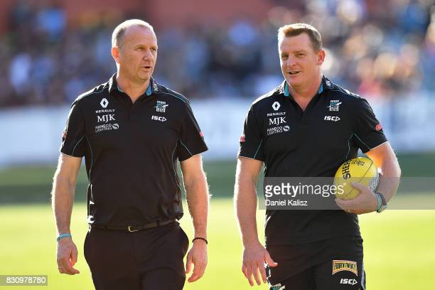 Ken Hinkley the coach of the Power and Michael Voss midfield manager of the Power walk from the field during the round 21 AFL match between Port...