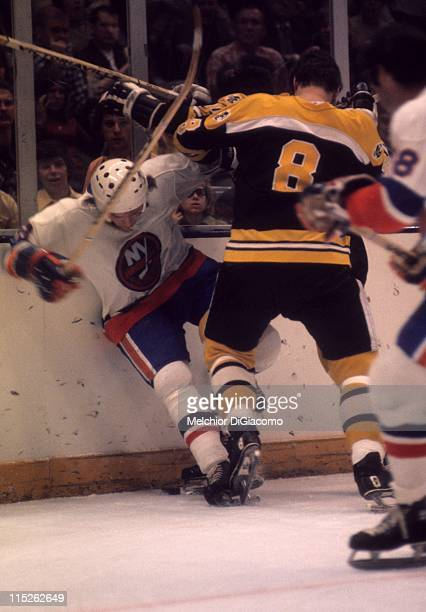 Ken Hodge of the Boston Bruins checks Garry Howatt of the New York Islanders into the boards during their game circa 1975 at the Nassau Coliseum in...