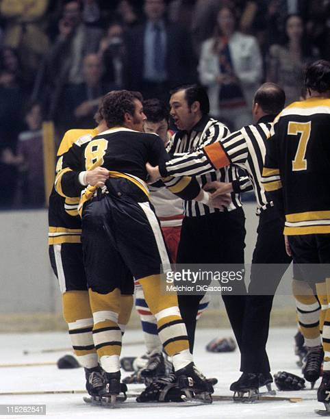 Ken Hodge of the Boston Bruins is held back by teammate Bobby Orr and the referee after fighting with a New York Rangers player circa 1972 at the...