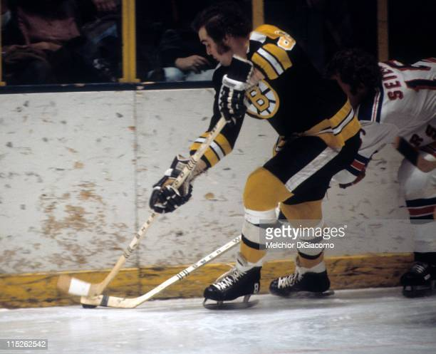 Ken Hodge of the Boston Bruins tries to control the puck as he gets pressured by Rod Seiling of the New York Rangers on January 4 1974 at the Madison...