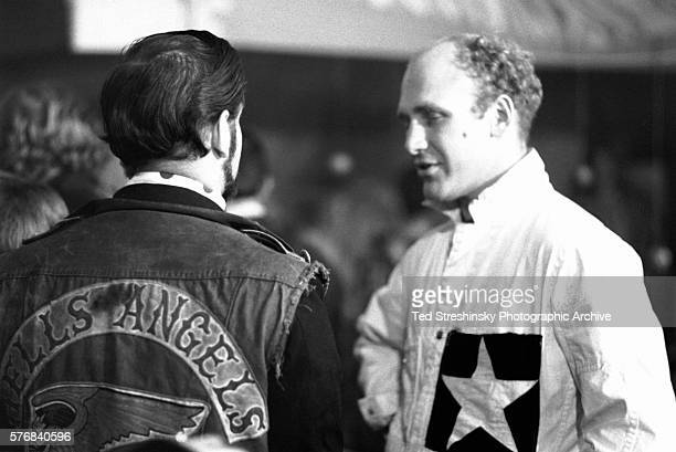 Ken Kesey author and leader of the psychedelic movement talks to a member of the Hell's Angels during the Merry Pranksters' Halloween Party also...
