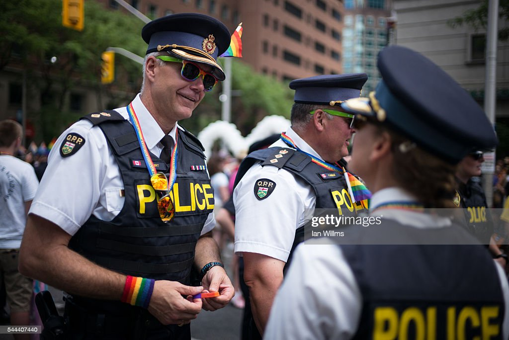 Ken Leppert (L) of the Ontario Provincial Police, speaks with colleagues at the annual Pride Festival parade, July 3, 2016 in Toronto, Ontario, Canada. Prime Minister Justin Trudeau will make history as the first Canadian PM to march in the parade.