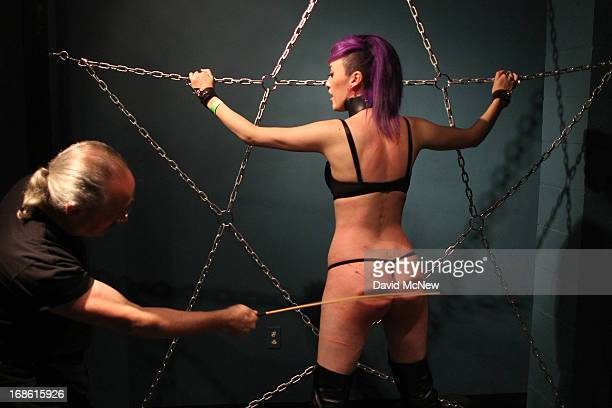 Ken Marcus canes voluntarily submissive Eva Mary at a dungeon party during the domination convention DomConLA on May 11 2013 in Los Angeles...