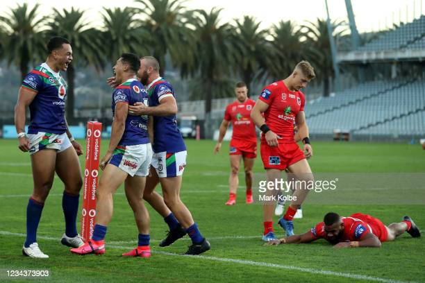 Ken Maumalo celebrates his try saving tackle with Roger TuivasaSheck as Mikaele Ravalawa of the Dragons lies dejected on the ground during the round...