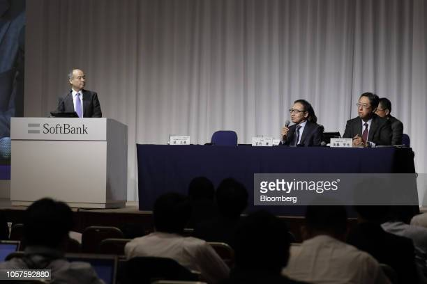 Ken Miyauchi, president and chief executive officer of SoftBank Corp., center, speaks as Masayoshi Son, chairman and chief executive officer of...