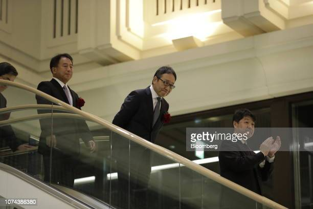 Ken Miyauchi, president and chief executive officer of SoftBank Corp., center, bows as he arrives for the company's listing ceremony at the Tokyo...