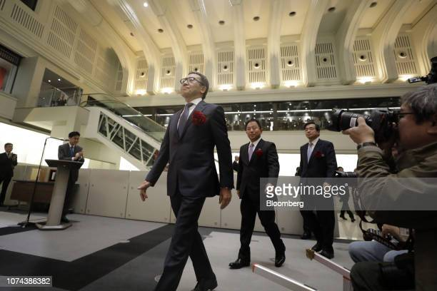 Ken Miyauchi, president and chief executive officer of SoftBank Corp., left, arrives for the company's listing ceremony at the Tokyo Stock Exchange...