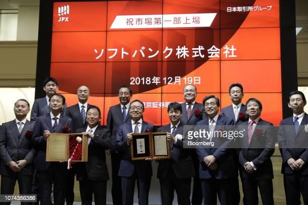 Ken Miyauchi, president and chief executive officer of SoftBank Corp., center left, and Yasuyuki Konuma, executive director of Tokyo Stock Exchange ,...