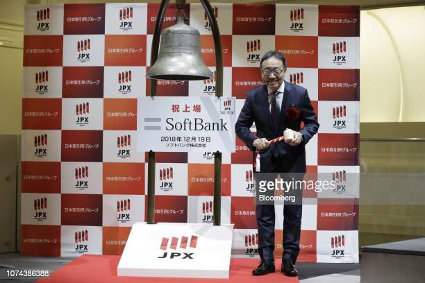 Ken Miyauchi, president and chief executive officer of SoftBank Corp., reacts before striking the trading bell during the company's listing ceremony...