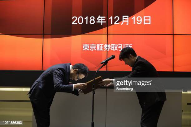 Ken Miyauchi, president and chief executive officer of SoftBank Corp., left, bows as he receives a certificate from Yasuyuki Konuma, executive...