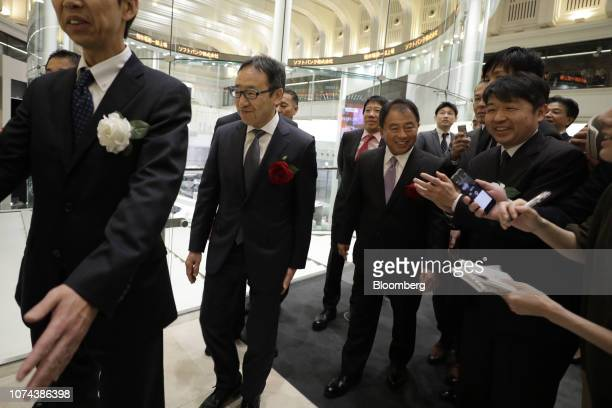 Ken Miyauchi, president and chief executive officer of SoftBank Corp., second from left, arrives for the company's listing ceremony at the Tokyo...