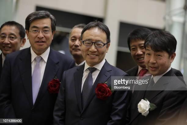 Ken Miyauchi, president and chief executive officer of SoftBank Corp., center, poses for a photograph with Yasuyuki Konuma, executive director of...