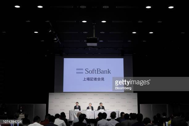 Ken Miyauchi, president and chief executive officer of SoftBank Corp., center, speaks while Junichi Miyakawa, chief technology officer, left, and...