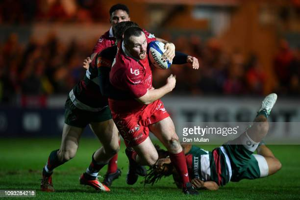 Ken Owens of Scarlets breaks the tackle of Kyle Eastmond of Leicester Tigers on way to scoring his side's second try during the Champions Cup match...