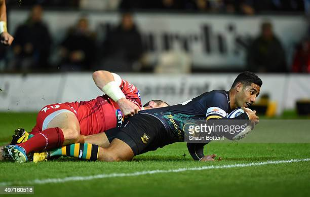 Ken Pisi of Northampton crashes over the tryline to score the opening try despite the tackle from Hadleigh Parkes of Scarlets during the European...