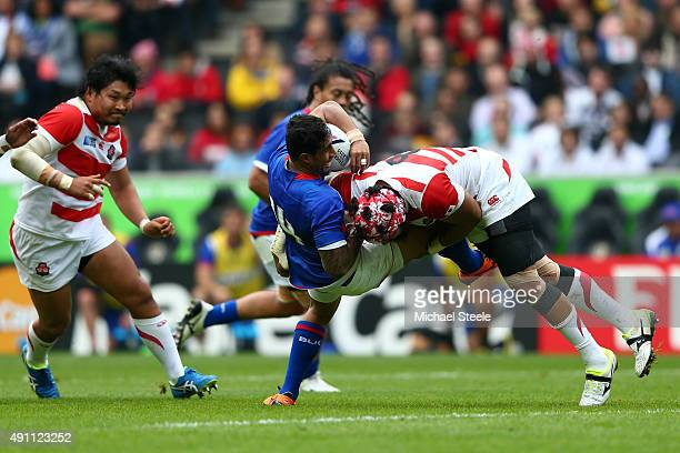 Ken Pisi of Samoa is tackled by Ryu Koliniasi Holani of Japan during the 2015 Rugby World Cup Pool B match between Samoa and Japan at Stadium mk on...