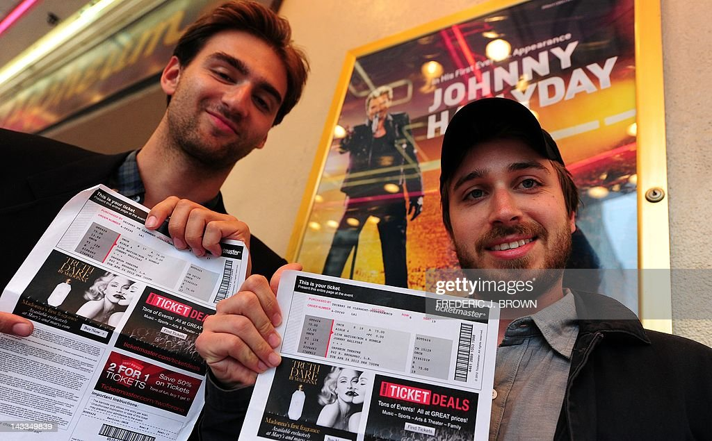 Ken Schlenker (L) and Thierry Declermont (R) display their tickets after travelling all the way from New York to see veteran French rocker Johnny Hallyday in his first concert in two years at the orpheum Theater on April 24, 2012 in Los Angeles, California, where Hallyday begins a comeback tour two years after a health scare which nearly killed him in his adopted home of Los Angeles. In a tribute to the city 'where they saved my life,' the 68-year-old will start the more than 50-show tour aiming to 'make the public tremble with emotion,' he told AFP earlier this month. AFP PHOTO/Frederic J. BROWN