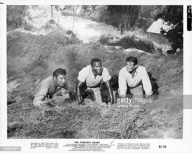 Ken Scott Rafer Johnson and Stuart Whitman crouching in ditch together in a scene from the film 'The Fiercest Heart' 1961