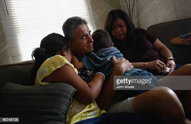 Ken Sheel terminally ill with pancreatic cancer embraces two of his children while seated next to his wife Jana during a home hospice visit on August...