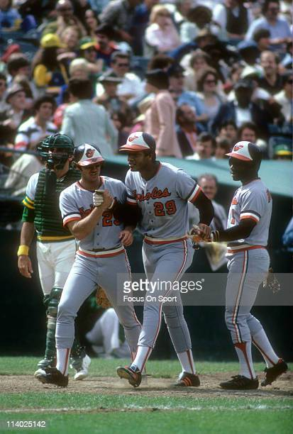 Ken Singleton of the Baltimore Orioles after hitting a home run against the Oakland Athletics is met by teammates Rich Dauer and Al Bumbry during a...