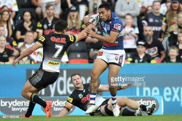 Ken Sio of the Knights evades the tackle of Nathan Cleary and Trent Merrin of the Panthers during the round four NRL match between the Penrith...
