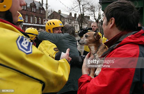 Ken Sugden and his rescued dog Kerry look on as Liz Fitton embraces an Inspector from the RSPCA rescue team after reuniting her with her dog Molly on...