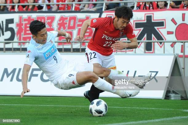 Ken Tokura of Consadole Sappolo and Yuki Abe of Urawa Red Diamonds compete for the ball during the JLeague J1 match between Urawa Red Diamonds and...