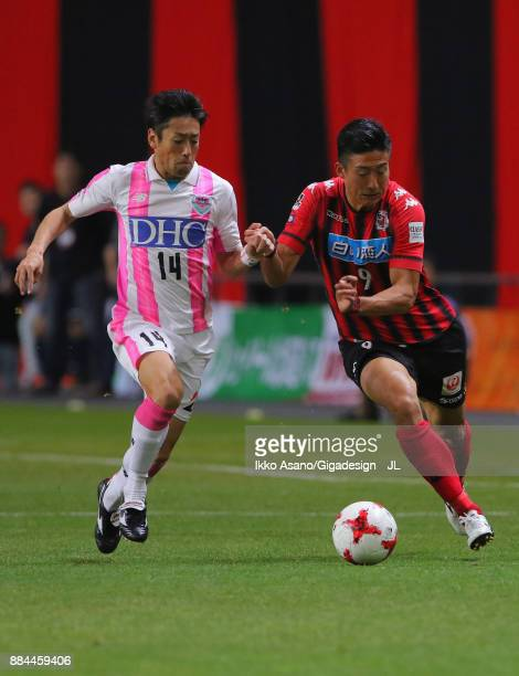 Ken Tokura of Consadole Sapporo and Yoshiki Takahashi of Sagan Tosu compete for the ball during the JLeague J1 match between Consadole Sapporo and...