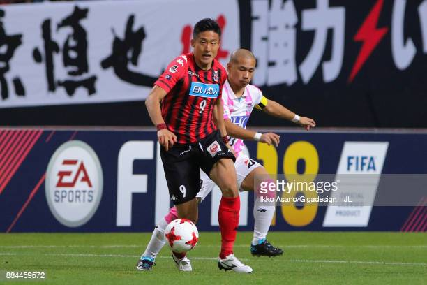 Ken Tokura of Consadole Sapporo controls the ball under pressure of Yutaka Yoshida of Sagan Tosu during the JLeague J1 match between Consadole...