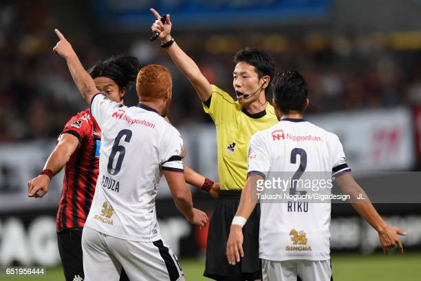 Ken Tokura of Consadole Sapporo, Souza and Riku Matsuda of Cerezo Osaka protest to referee Atsushi Kamimura during the J.League J1 match between...