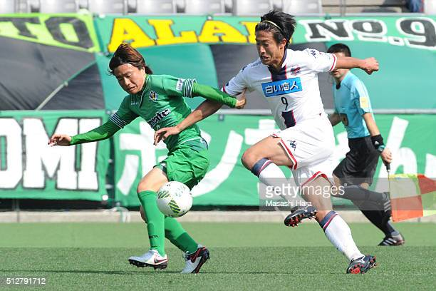 Ken Tokura of Hokkaido Consadole Sapporo and Kazuki Anzai of Tokyo Verdy compete for the ball in during the J.League second division match between...