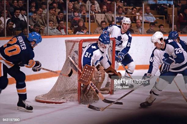 Ken Wregget Al Iafrate and Chris Kotsopoulos of the Toronto Maple skates against Mark Hunter of the St Louis Blues during game action on December 11...
