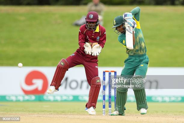 Kenan Smith of South Africa bats while wicketkeeper Emmanuel Stewart of the West Indies looks on during the ICC U19 Cricket World Cup match between...
