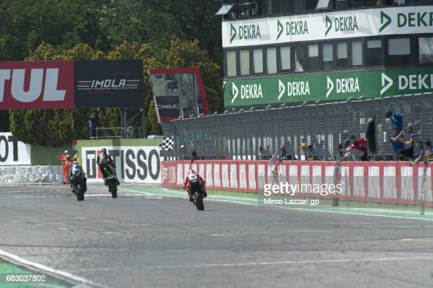 Kenan Sofuoglu of Turkey and Kawasaki Puccetti Racing cuts the finish lane and celebrates the victory on podium during the SuperSport Race during the...