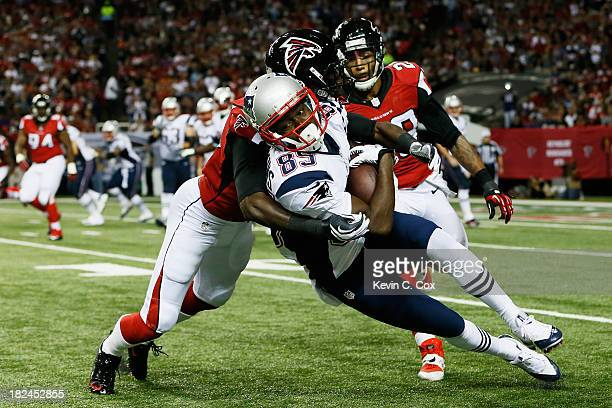 Kenbrell Thompkins of the New England Patriots is tackled by Desmond Trufant and Thomas DeCoud of the Atlanta Falcons during the game at Georgia Dome...