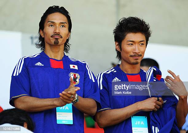Kenchi and Makidai of the allmale Japanese pop band and dance group Exile watch on during the Japan v Ivory Coast International Friendly match at...