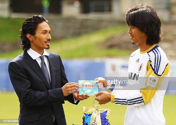 Kenchi of the allmale Japanese pop band and dance group Exile presents a gift to Yuji Nakazawa during a visit to a Japan training session at SaasFee...