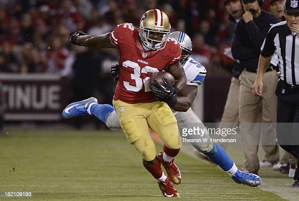 Kendall Hunter of the San Francisco 49ers gets dragged out of bounds by Stephen Tulloch of the Detroit Lions in the third quarter of an NFL football...