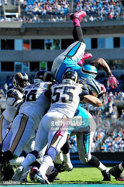 Kendall Langford and James Laurinaitis of the St Louis Rams stop Mike Tolbert of the Carolina Panthers short of the goal line during play at Bank of...