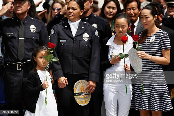 LOS ANGELES CA THURSDAY MAY 8 2014 Kendall Lee left holds onto a rose with one hand and the hand of LAPD officer Rosalind Curry with the other Lee's...