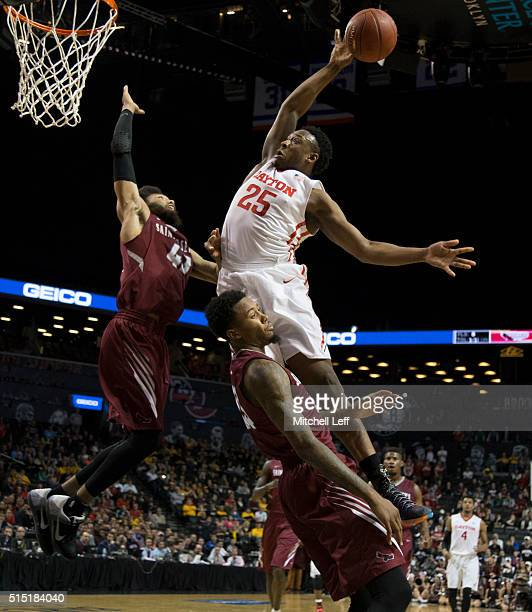Kendall Pollard of the Dayton Flyers charges into Isaiah Miles of the Saint Joseph's Hawks in the semifinals round of the men's Atlantic 10...