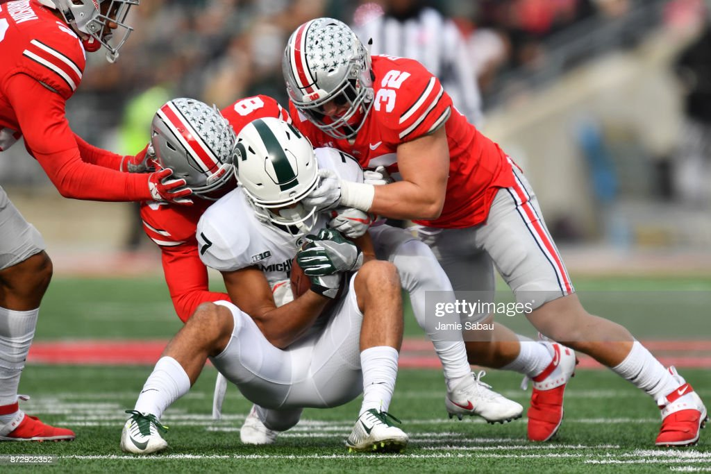 Kendall Sheffield #8 of the Ohio State Buckeyes and Tuf Borland #32 of the Ohio State Buckeyes wrap up Cody White #7 of the Michigan State Spartans after a short gain in the third quarter at Ohio Stadium on November 11, 2017 in Columbus, Ohio. Ohio State defeated Michigan State 48-3.