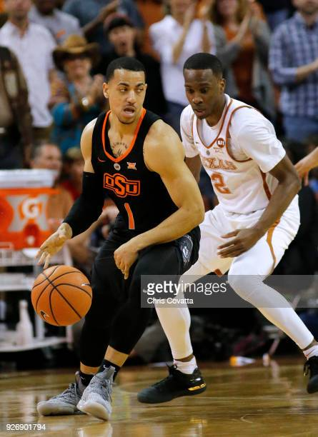 Kendall Smith of the Oklahoma State Cowboys moves around Matt Coleman of the Texas Longhorns at the Frank Erwin Center on February 24 2018 in Austin...
