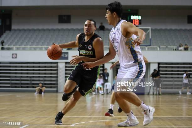 Kendall Stephens drives to the basket against Liu Yuanyu of Jiangsu Dragons during the Victoria-Jiangsu Basketball Friendship Game match between...