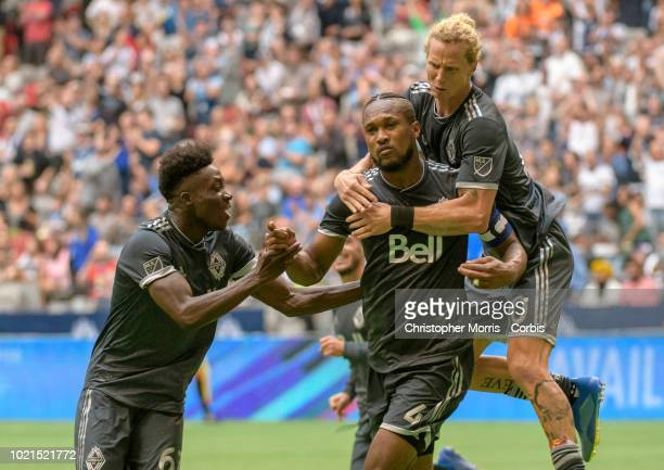 Kendall Waston celebrates with teammates Alphonso Davies and Brek Shea of the Vancouver Whitecaps after scoring a goal at BC Place on August 18 2018...