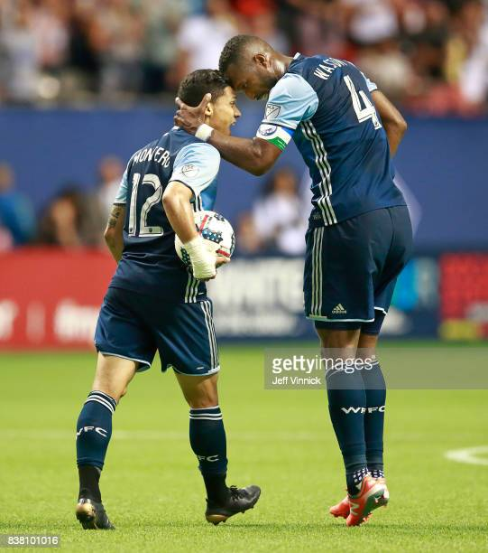 Kendall Waston of the Vancouver Whitecaps FC congratulates teammate Fredy Montero after scoring on the Seattle Sounders during their MLS game August...