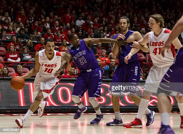 Kendall Williams of the New Mexico Lobos runs the ball to the basket around defender Jerome Garrison of the Grand Canyon Antelopes during the game...