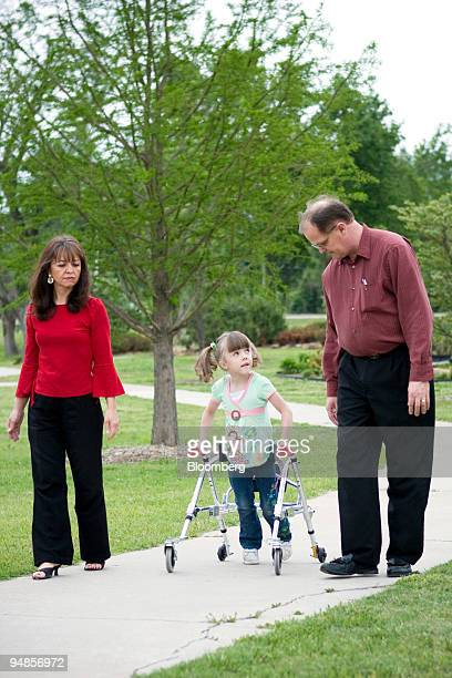 Kendra Dyer center walks with her parents Marshall right and Natia at a park in Broken Arrow Oklahoma US on Tuesday May 6 2008 Kendra was born four...